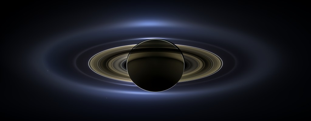 Saturn, as seen from Cassini, with Earth faintly glowing in the background.  Credit: NASA/JPL-Caltech/Space Science Institute
